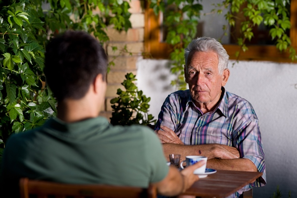 older man unhappily speaking to younger man