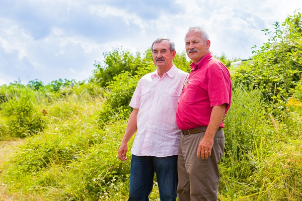 two older gentleman in a beautiful green field